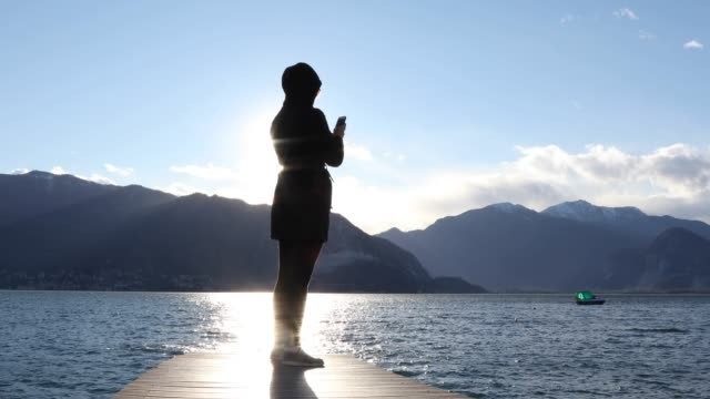 woman walks onto lake pier, takes smart phone pic - see other clips from this shoot 56 stock videos & royalty-free footage