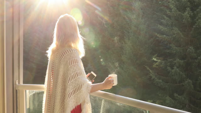woman walks onto outdoor deck holding hot drink and smart phone - aussicht genießen stock-videos und b-roll-filmmaterial