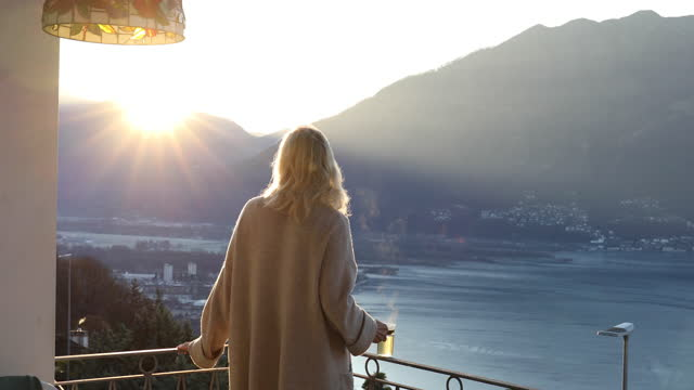 woman walks onto rooftop terrace at sunrise - tea cup stock videos & royalty-free footage