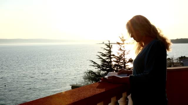 woman walks onto terrace with magazine, sunrise - magazine stock videos & royalty-free footage