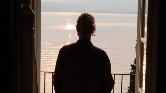 woman walks onto veranda at sunrise - piemonte video stock e b–roll