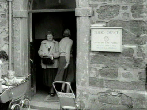 a woman walks out of a food office based in a church and puts her ration book into her handbag 1954 - food stamps stock videos & royalty-free footage