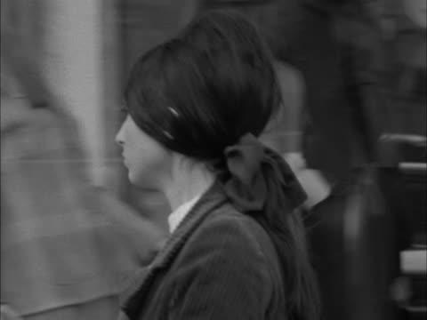 stockvideo's en b-roll-footage met a woman walks out of a shop wearing a corduroy trouser suit - dameskleding
