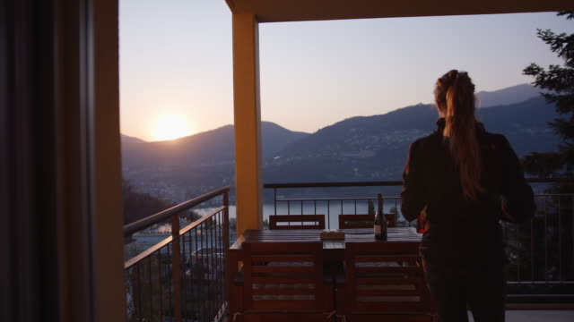 vídeos de stock e filmes b-roll de woman walks out on balcony after work to watch sunset and prepare beverage - jaqueta jeans
