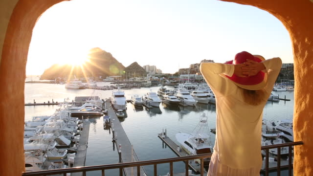woman walks out onto deck above marina, sunrise - cabo san lucas stock videos & royalty-free footage