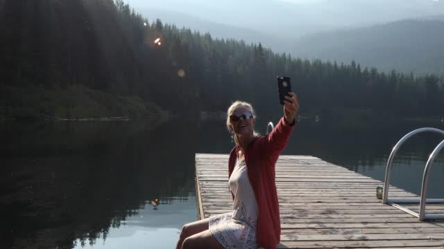 kvinna går på piren vid soluppgången, i bergen - endast en medelålders kvinna bildbanksvideor och videomaterial från bakom kulisserna