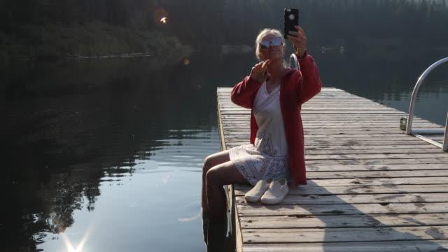 frau geht raus auf pier bei sonnenaufgang, in bergen - dreiviertelansicht stock-videos und b-roll-filmmaterial