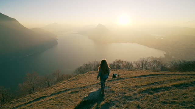 Woman walks out to viewpoint over lake at sunset