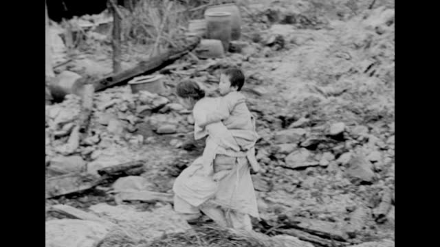 woman walks over a field of debris with a child on her back in south korea during the korean war. - korean war stock videos & royalty-free footage