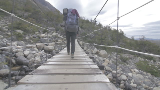 woman walks over suspension bridge - tracking shot stock videos & royalty-free footage