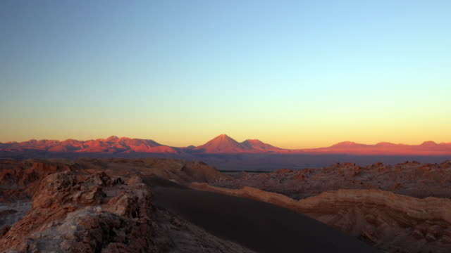 woman walks over the mountain while the last day light hits the andes cordillera mountains in the distance. - 乾燥気候点の映像素材/bロール