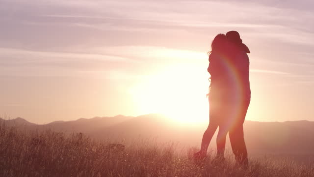 Woman walks over to man to hug and kiss him during sunset
