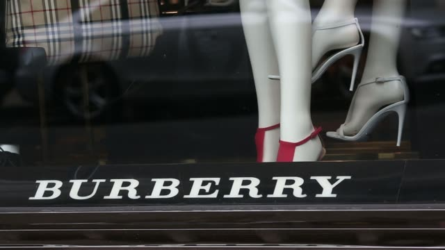 A woman walks past a Burberry fashion store operated by Burberry Group Plc on New Bond Street in London UK on Wednesday May 21 A white leather...