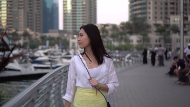 Woman walks past bay in Dubai, tracking shot