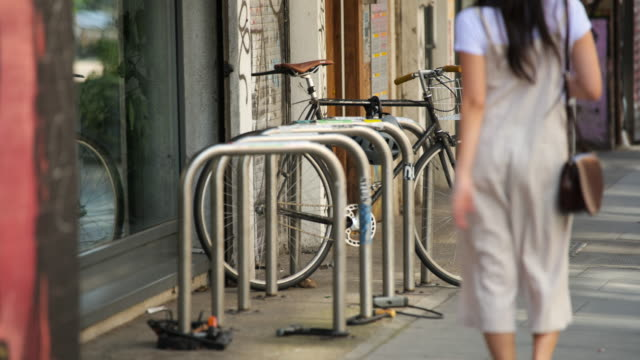 woman walks past bike in shoreditch, london - boundary stock videos & royalty-free footage