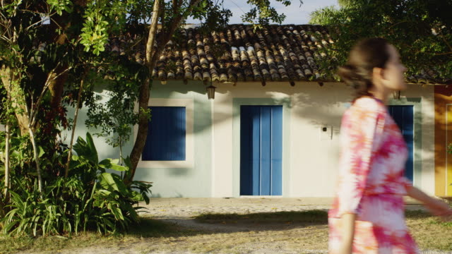 ms a woman walks past colonial houses in trancoso / trancoso, brazil - kolonialstil stock-videos und b-roll-filmmaterial