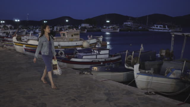 vídeos de stock, filmes e b-roll de woman walks past docks at night, tracking shot - jaqueta jeans