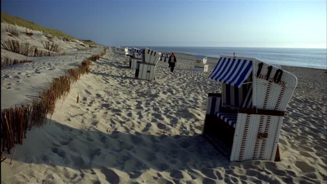 WIDE SHOT woman walks past empty cabanas on beach / island of Sylt, Schleswig-Holstein, Germany