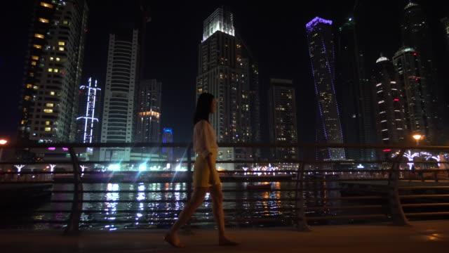 woman walks past skyscrapers at night, dubai - nightlife stock videos & royalty-free footage