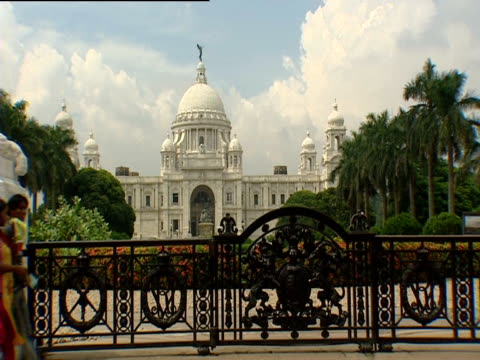 woman walks past victoria memorial hall - victoria memorial kolkata stock videos and b-roll footage