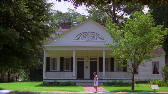 Woman walks past white timber house in leafy-green neighborhood as car drives by, Natchez, Mississippi Available in HD.