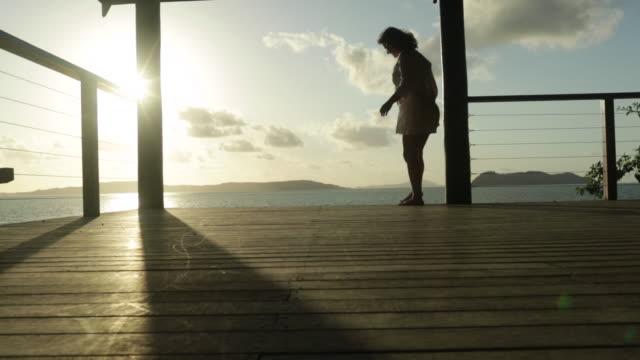 Woman walks playfully across veranda and balances along edge of deck.