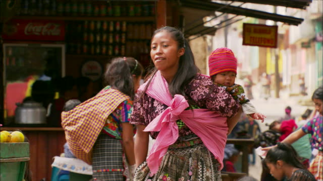 woman walks though street market carrying child in sling available in hd. - guatemala stock videos & royalty-free footage