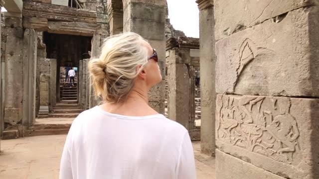 Woman walks through Ancient ruins, in awe