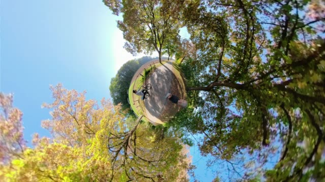 a woman walks through colorful autumn trees with little planet effect - fish eye lens stock videos & royalty-free footage