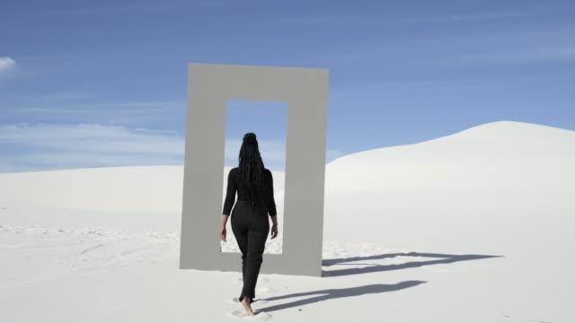 woman walks through door frame in desert, wide - eintreten stock-videos und b-roll-filmmaterial
