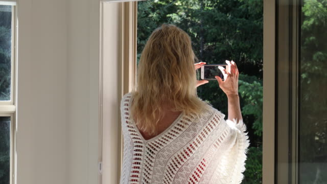 woman walks through doorway to photograph forest view - one mature woman only stock videos & royalty-free footage