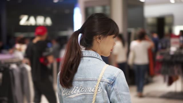 vídeos de stock, filmes e b-roll de woman walks through retail stores in mall, close up - jaqueta jeans