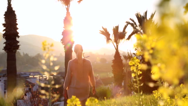 vidéos et rushes de woman walks through sunny glade below palms, mosque - islam