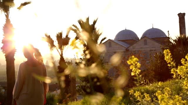 woman walks through sunny glade below palms, mosque - izmir stock videos & royalty-free footage