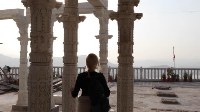 woman walks through temple courtyard in stockings - tempio video stock e b–roll