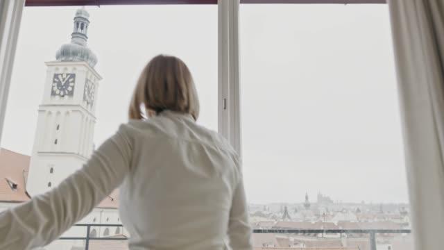 stockvideo's en b-roll-footage met ws vrouw loopt naar een balkon van haar appartement in de stad - balkon