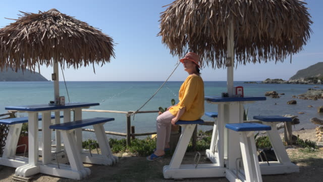 pan/ a woman walks to a beach bar and looks out to the sea - straw hat stock videos and b-roll footage