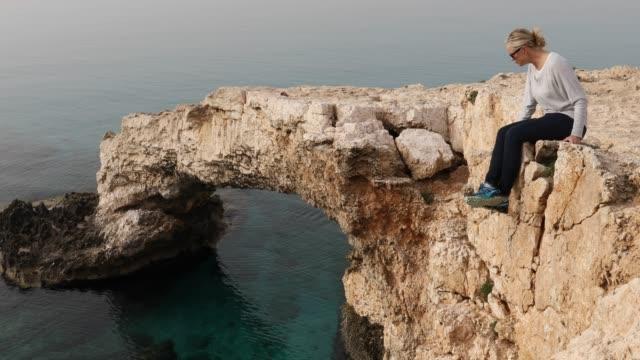 Woman walks to edge of natural rock bridge, looks off