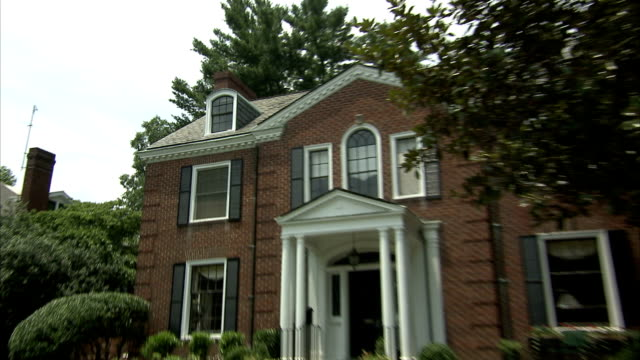 a woman walks to the front door of a stately two-story home. - pediment stock videos & royalty-free footage