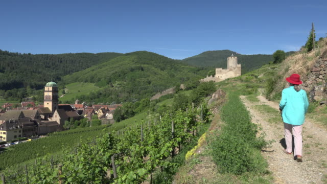 a woman walks to village with castle and makes photos - french culture stock videos & royalty-free footage