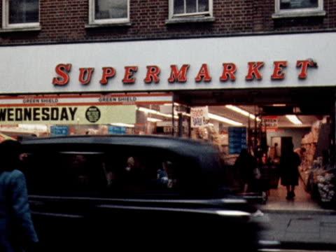 vídeos de stock e filmes b-roll de a woman walks toward a high street supermarket - vendas