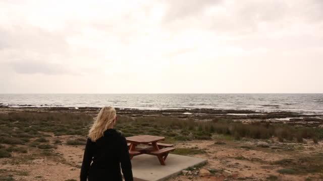 Woman walks towards beach picnic table, pauses to admire sea