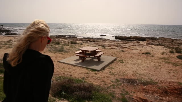 woman walks towards beach picnic table, pauses to admire sea - picnic table stock videos and b-roll footage