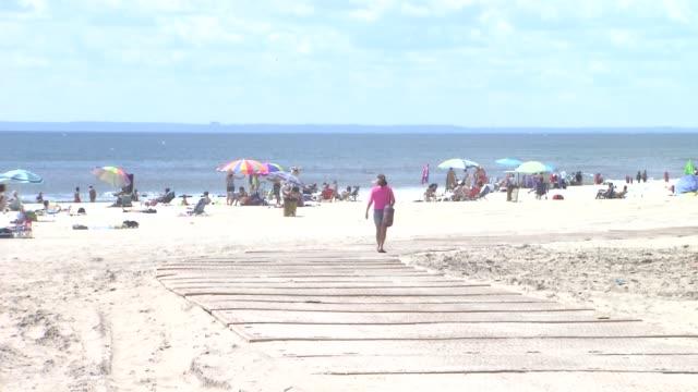 vídeos y material grabado en eventos de stock de far rockaway beach opens to the public after hurricane sandy woman walks towards beach on august 04 2013 in new york new york - queens