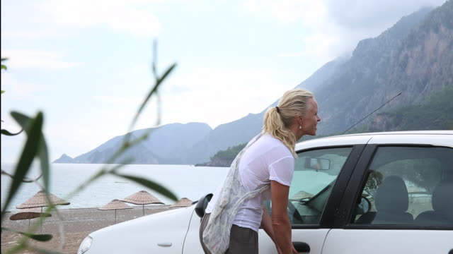 woman walks towards car, parked on beach - haar nach hinten stock-videos und b-roll-filmmaterial