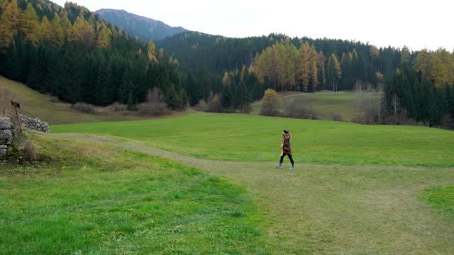 vidéos et rushes de woman walks towards small church at the end of valley - châle