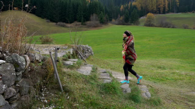 woman walks towards small church at the end of valley - kosmetisches stirnband stock-videos und b-roll-filmmaterial