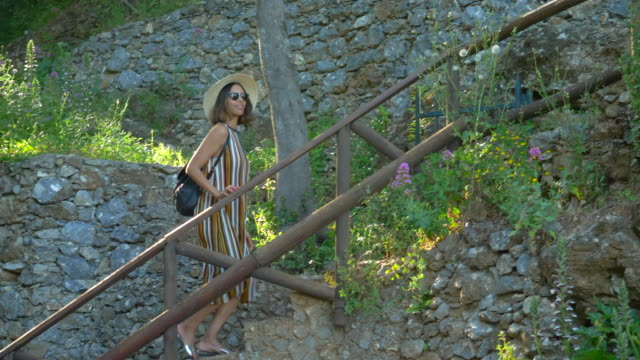 a woman walks up stairs at a mediterranean sea beach club in a luxury resort town in italy, europe. - slow motion - steps stock videos & royalty-free footage