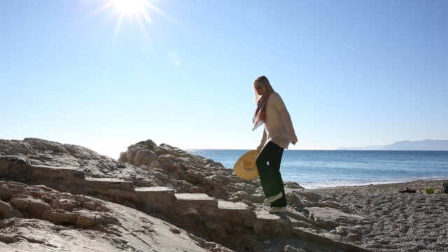 woman walks up stone staircase above beach, into sunlight - 沿岸点の映像素材/bロール