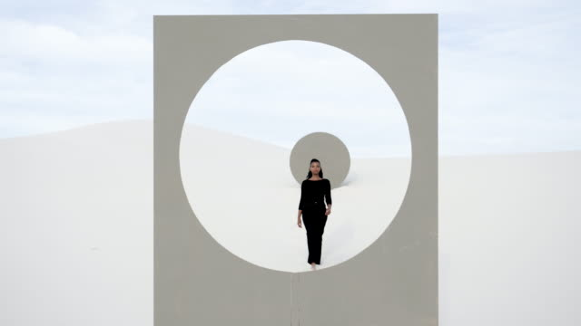 vidéos et rushes de woman walks up to placard with circle window frame in desert - mannequin métier